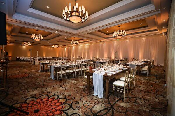 SandPearl Resort ballroom set with soft neutrals and wooden farmhouse tables