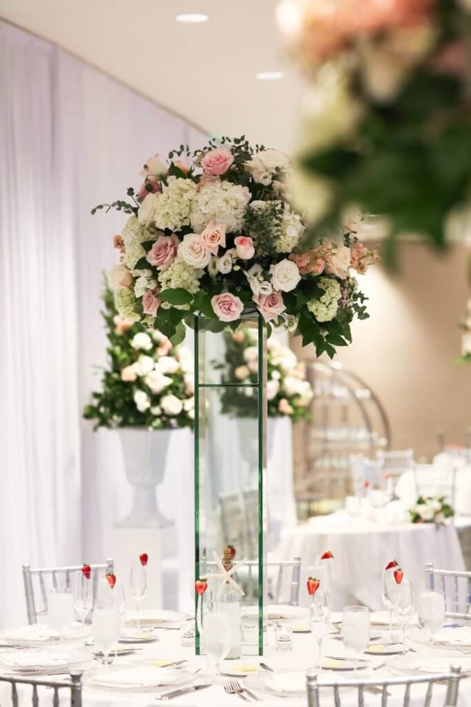 tall pink and white centerpieces resting on glass pillars
