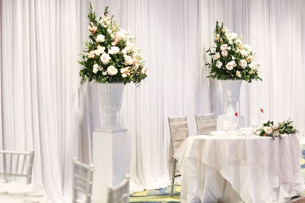 sweetheart table flanked by floral pieces repurposed from the ceremony