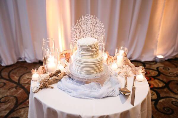 unique wedding cake surrounded by coral, shells and driftwood