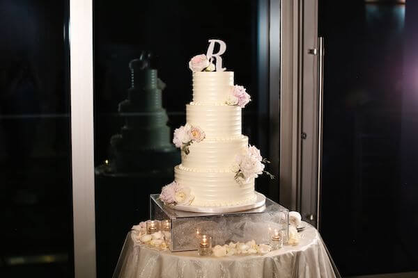 four tiered white buttercream wedding cake with pink flowers and' R' monogram cake topper
