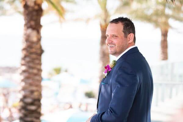 groom wearing a navy-blue suite with a tropical boutonniere