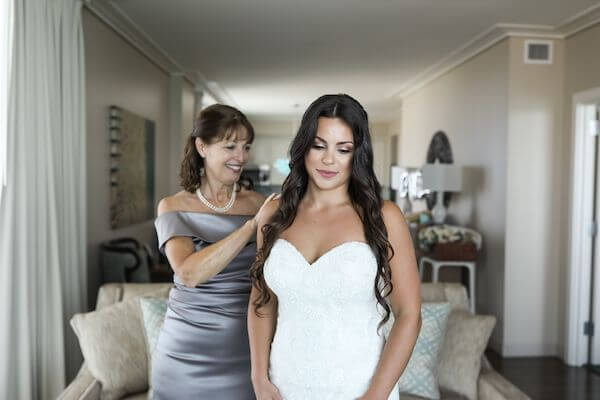 mother of the bride helping her daughter with wedding jewelry