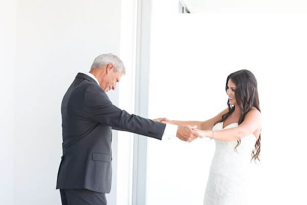 father looking at his daughter for the first time on her wedding day