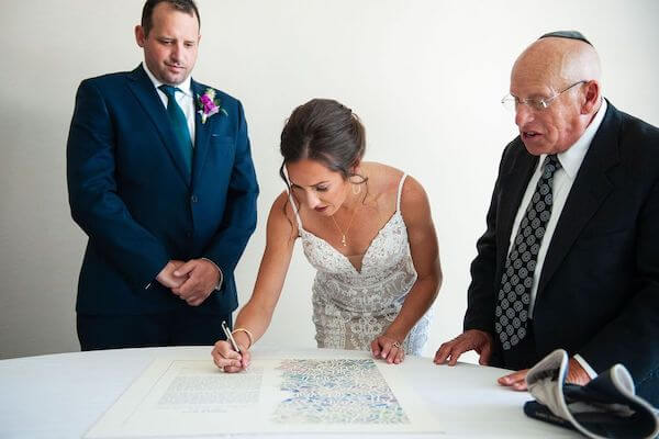 bride signing the ketubah as her groom-to-be and Rabbi look on