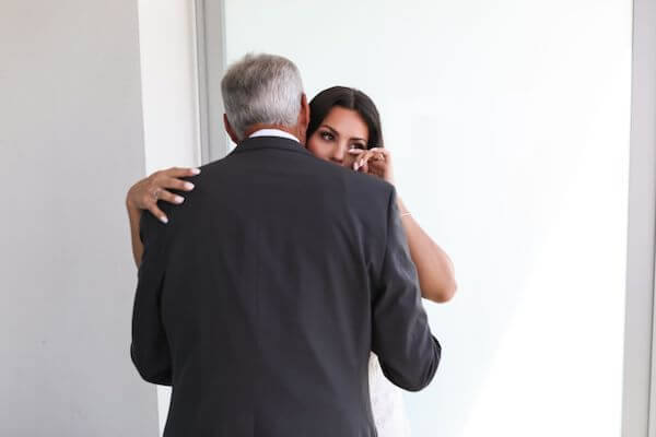 bride tearing up after seeing her dad for the first time on her wedding day