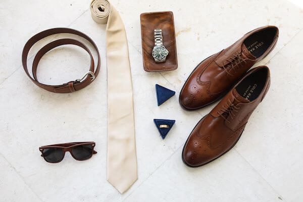 flat lay of groom's wedding accessories in browns and neutral tones