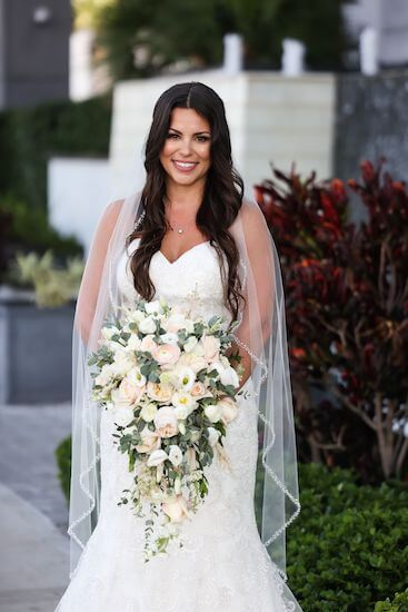 bride wearing a lace appliqué wedding gown with sweetheart neckline carrying a blush and white cascading bouquet