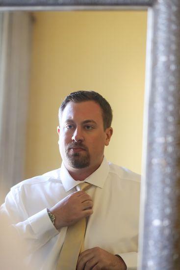 groom looking in the mirror fixing his tie