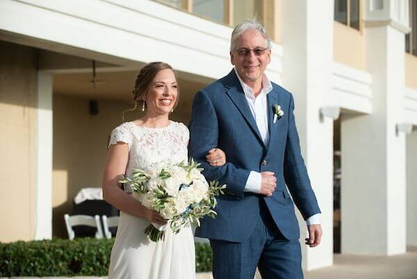bride to be smiling ear to ear as her father walks her down the aisle