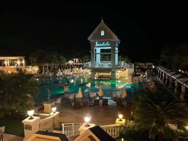 night time view of pool and lit up Sandals sign