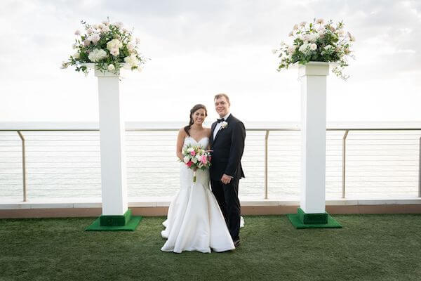 bride and groom posing for photos after their Clearwater Beach wedding ceremony