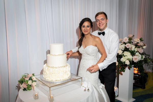 bride and groom cutting their wedding cake at their Opal Sands Resort wedding reception