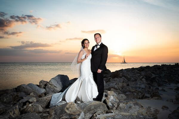 Sailboat and Sunset behind newlywed couple on Clearwater Beach