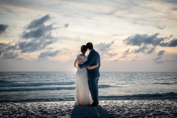 bride and groom arm and arm on Clearwater beach at sunset