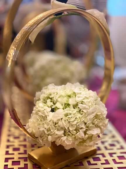 wedding centerpiece with gold rings and white hydrangea
