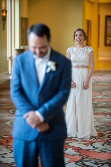 bride walking up behind her groom during their first look