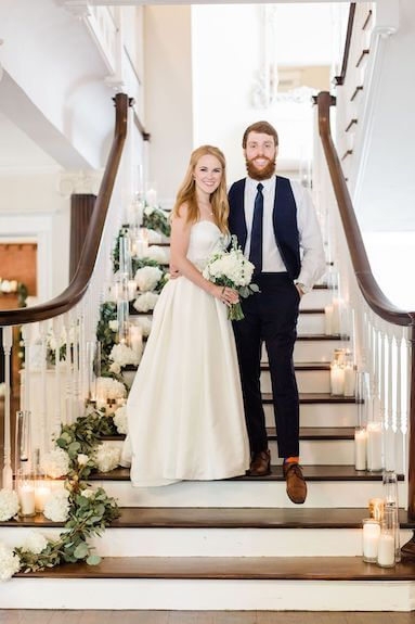 Bride and groom posing for photos on the Grand Staircase of The Orlo