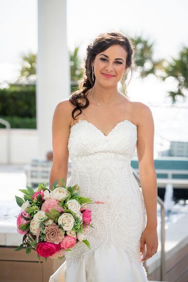 bride in lace wedding gown holding a textured pink and white bouquet