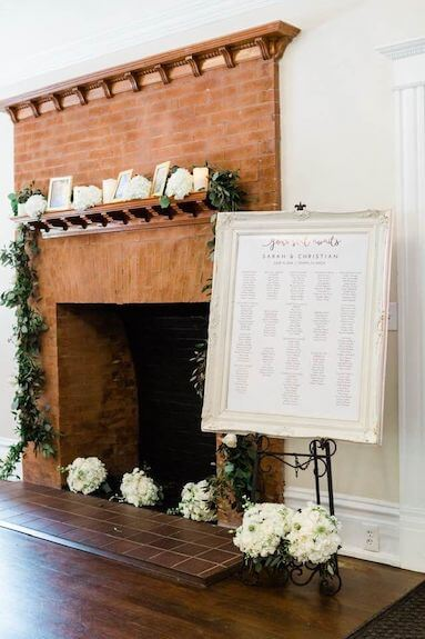 Brick fireplace at The Orlo decorated with candles, flowers and family photos