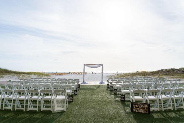 LOVE IS signs line the aisle at a Clearwater Beach wedding ceremony