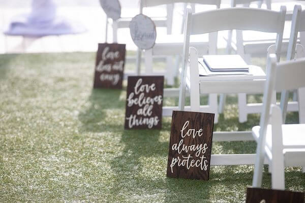 wooden LOVE IS signs with quotes from 1 Corinthians lining the aisle at a clearwater Beach wedding ceremony