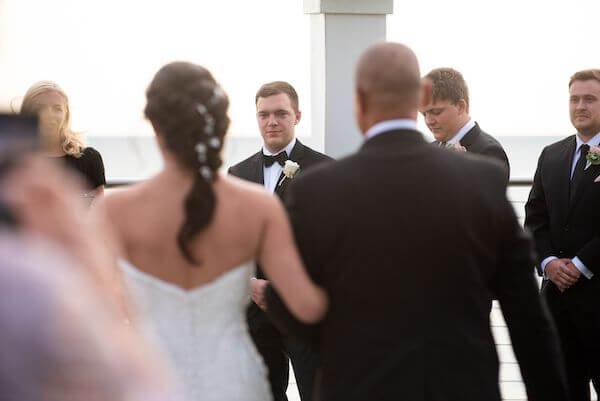 Groom watching as his bride-to-be walks down the aisle during their Clearwater Beach wedding