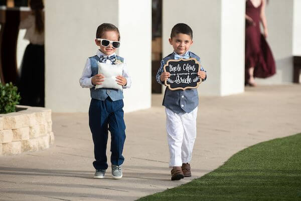 ring bear and another little guy carrying a here comes the bride sign at a Clearwater Beach wedding ceremony