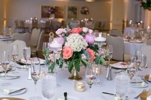 pink floral centerpieces on gold risers at a clearwater Beach wedding reception