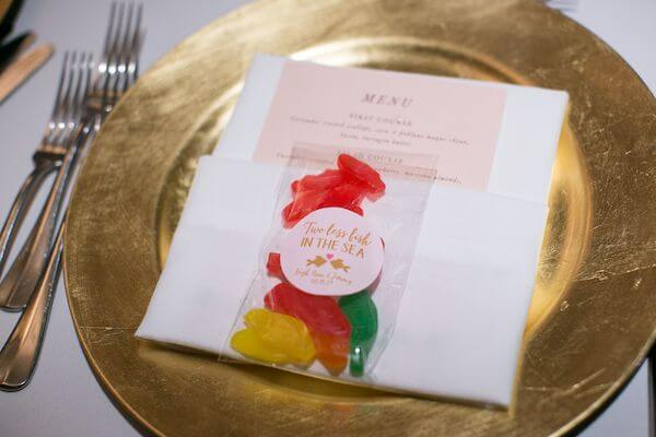 gold charger plate with a custom menu card and a wedding favor with Swedish fish for a beach themed wedding reception