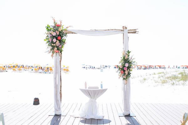 wedding arch on Clearwater beach decorated with pink flowers and fabric