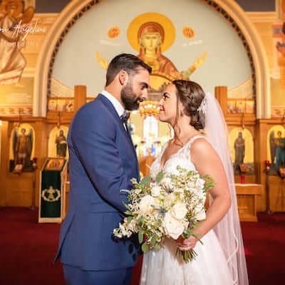 bride and groom pose for pictures after Greek Orthodox wedding during COVID